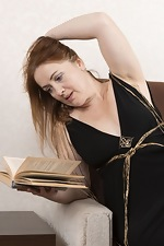Gloria G strips naked while reading a book